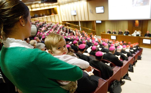 A mother holds her child as she observes a session of the Synod of Bishops on the family at the Vatican Oct. 24. (CNS photo/Paul Haring) See SYNOD-FINAL Oct. 24, 2015.